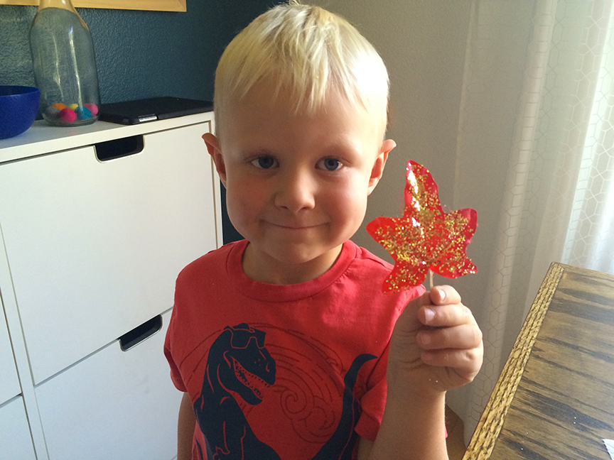 To make these glitter leaves, spread glue on fake leaves and sprinkle on glitter. Great fall craft!
